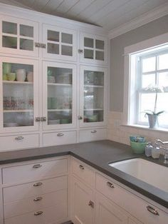 Painted cabinets and the bin pull silver hardware, a few glass fronts; the counters are a quartz composite called caesarstone, in a color called either cement or concrete.