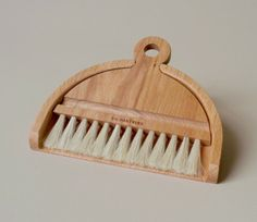 Oiled beech and horsehair brush and dustpan set designed for cleaning tabletops, shelves, and other small surfaces.