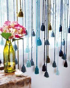 Curtains with knit I cord tassels of different lengths, in shades of similar colours.