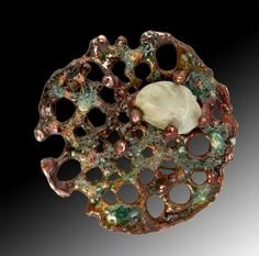 Evelyn Markasky, Copper with holes burned and silver melted on, with layers of enamel and sand, polished pebble, brass pin