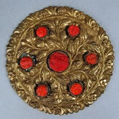Register 1954: Woman's hair ornament made of yellow metal disk with repousse floral ornament and seven studs of red composition; copper pin on back.