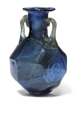 A ROMAN BLUE MOULD-BLOWN GLASS FLASK  CIRCA 1ST CENTURY A.D.  The octagonal body with central concentric rings on each side, the neck with everted rim and applied pale green twin handles, with flattened rectangular base  3 1/8 in. (8 cm.) high