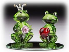 Princess and the Frog - A pair of green Lovesick Frogs spun glass sculpture. Cute spun glass frog prince offers a pink rose to his ruby heart struck frog lady love as they sit on a reflective pond mirror base. This hand made spun glass figurine is a perfect gift or wedding favor.