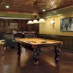 Vintage-style light fixtures, dark wood finishes, a coppery ceiling, and faux-leather upholstered walls create an elegant setting for this basement billiards and poker game room. | Photo: Mark Samu | thisoldhouse.com