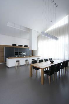 Black kitchen units tie-in with the other black accents in the room, found in the dining chairs, bar stools and statement cabinets.