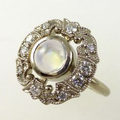 Moonstone and diamond stylised dress ring in 9 carat white gold.