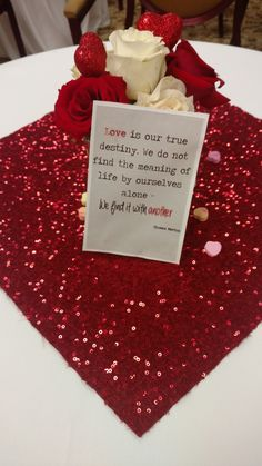 Sparkly red fabric cut into squares for centerpieces. Rose floral arrangements surrounded by scattered candy hearts. Love quote found on pinterest and glued to cardstock. Used these centerpieces at a cooking demo around Valentine's Day.  #valentinesday #love #hearts #roses #centerpieces #decor #sparkle #red #amour