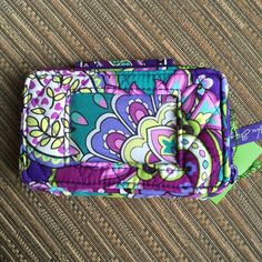 "Vera Bradley Smart Phone Wristlet NWT~Heather Vera Bradley Smart Phone Wristlet NWT~Heather • Larger all-in-one phone case and wallet • Zip-around compartment reveals three card slips, a bill compartment, a coin purse and an outer ID window. • Fits an iPhone 5/5s in an OtterBox Case • Wallet strap I clips to wrap it around a handbag or tote handle. • The snap flap on the phone compartment is secure, yet easy to access. Size: 5 1/2"" W x 3 1/4"" H x 2"" D with 6"" wrist strap~SMOKE FREE HOME…"
