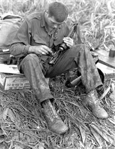 Soldier of the 101th Airborne while cleaning his  XM16E1 rifle somewhere in Vietnam.The U.S. Army XM16E1 was essentially the same weapon as the M16 with the addition of a forward assist and corresponding notches in the bolt carrier.To address issues raised by the XM16E1's testing cycle, a closed, bird-cage flash suppressor replaced the XM16E1's three-pronged flash suppressor which caught on twigs and leaves. Various other changes were made after numerous problems in the field.