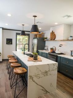 marble counter tops, dark gray bottom cabinets, white subway tile and wooden stools