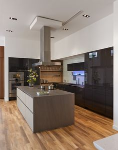"""SieMatic PURE, S2, lacquer, graphite grey gloss, nickel gloss integrated grip slot (cabinets/panels), Floating Spaces, wood veneer, titan oak matte (wall/shelf system), wall shelf with integrated task and LED atmospheric lighting Gaggenau: Combi-Steam Oven, Oven, Warming Drawer, 18"""" Fully-Integrated Freezer Column, 24"""" Fully-Integrated Refrigerator Column, Full-Surface Induction Cooktop, Island Hood, stainless steel Dornbracht: Lot mixer, water dispenser and hand spray, polished chrome"""