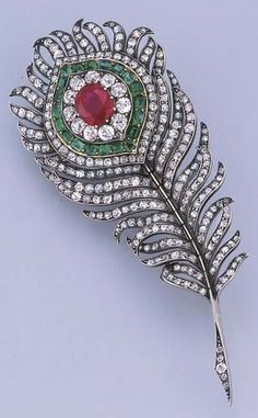 A FINE ANTIQUE DIAMOND AND GEM-SET FEATHER BROOCH. Designed as a peacock feather set en tremblant, the central cushion-cut ruby within diamond and emerald surround to the old-cut diamond plumes and quill, mounted in silver and gold, circa 1890, 8.7 cm. long, in original Catchpole and Williams Ld (late C J Hill) 510 Oxford St.W, blue velvet case.