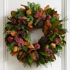 Holiday Fruit Wreath--fresh magnolia, cedar and green salal mixed with austriaca cones, pepperberries, pomegranates, quince slices, faux red apples and air-dried slit oranges #williamssonoma