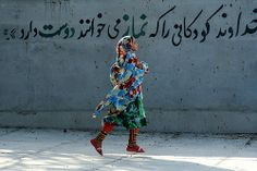 "Iran, 2011:   A girl passes a wall that reads: ""God loves children who say their 'namaz' (prayers).""  She is on her way to her kindergarten, in the village of Bahl, Hormozgan Province.  Article 14 of the Convention on the Rights of the Child guarantees every child's right to freedom of thought, conscience and religion. UNICEF works worldwide to realize the fulfilment of all children's rights. by UNICEF HQ"