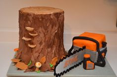"Tree and Chainsaw cake - Six 8"" cakes stacked. Made the chainsaw out of a cake baked in a 8"" x 4"" loaf pan, cut in half and stacked. Blade was cardboard and pipe cleaners. Mushrooms, top of log, chainsaw details and oil bottle were modeling chocolate"