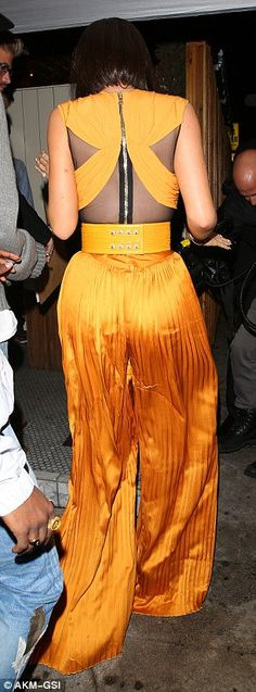Pleats to see you: The voluminous fabric of the burnt orange garment draped over her figure