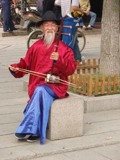 Elderly musician on the street in a watertown in China