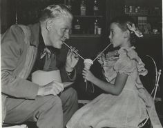 From an original negative, photo of Nelson Eddy and a very young Natalie Wood sharing an ice cream treat. - ESCANO COLLECTION
