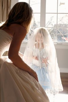 Flower girl trying on the bride's veil
