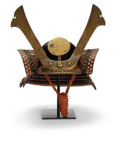 """A Myochin school suji kabuto By Nobuie, Edo period (18th century) The sixteen-plate kabuto lacquered black and fitted with gilt-brass mounts including a four-stage tehen kanamono, kuwagata-dai carved with chrysanthemums, the mabizashi applied with stenciled leather and """"rope"""" fukurin,"""
