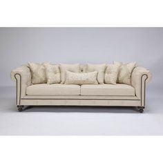 This traditional sofa gets a modern twist using richly textured linen blend fabrics and antique nail-head detailing. Classic touches like button tufting and ash stained legs finish the piece. Included are seven throw pillows to complete the sofa.