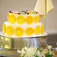 2段のウェディングケーキは人気のフルーツ断面ケーキです。柑橘系の爽やかなケーキが夏らしさを感じますね!ケーキフラワーはご新婦さまが用意され、節約されたのだとか。