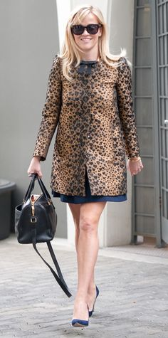 Reese Witherspoon showed off a fiercer side with a heart-shaped leopard print coat layered over a navy frock, accessorizing the two with a black handbag and navy suede pumps.  #InStyle