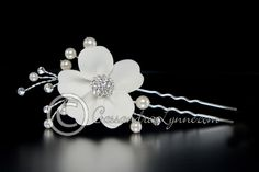 A handmade ivory matte satin flower bridal hair pin with a rhinestone jewelled center and ivory pearl sprays. Length of pin including the decoration is 4 inche