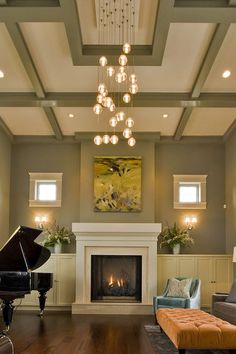 Coffered ceiling is painted to pull the wall color upward; designed in a way that highlights the contemporary light fixture in the center.
