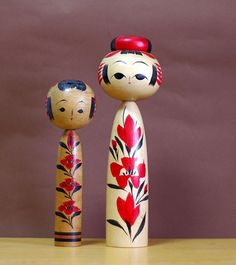creative kokeshi dolls with red flowers.