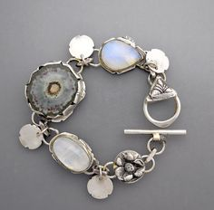 A sterling silver bracelet with hand fabricated sterling flower elements, a beautiful polished agate stalactite slice and two natural moonstone cabochons.  Seven inches in length.