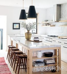 Introducing wood bases and shelves with the marble counters and backsplash feels rustic and elegant. | Photographer: Alex Lukey | Designer: Sam Sacks