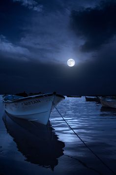 Full moon rising over the sea, with moonlight shining on the boats.   Photography by Kenan Budakoglu
