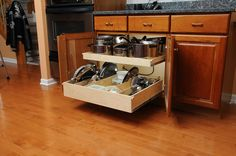 This #KitchenCabinet beside the oven became the perfect place to store pots and pans after removing the center stile and adding #PullOutShelves and some dividers for #LidStorage.  http://www.shelfgenie.com/