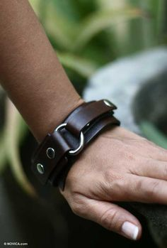 Shining studs decorate a wide leather strap in a bold brown wristband. By Java's Hariyono, it features narrower straps that loop through an iron ring and double back to snap closed.