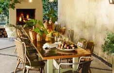 A leaf-covered patio gets a romantic upgrade with vintage furniture, mood lighting, and a party-ready trestle table