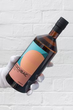 A white gloved hand holding a bottle of Escubac