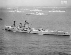 The British battleship HMS NELSON off Spithead for the 1937 Fleet Review. Anchored in the background are two Queen Elizabeth Class battleships and two cruisers of the London Class.