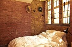 Ain't nothing wrong with beautiful all-white bedding! Especially against these stunning exposed brick walls.