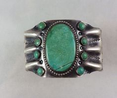 Wide silver cuff with a large green oval turquoise is hand crafted in the Fred Harvey souvenir jewelry style.