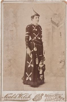 """tuesday-johnson: """"ca. 1870-90s, [advertising cabinet card of a woman wearing a dress affixed with various wares, including nails, spoons, chain links, and a funnel. Inked on verso 'Irma Z. Smith/Cadillac, Mich.'] Neal & Welsh """""""