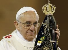 Pope Francis holds up a statue of Our Lady of Aparecida at the beginning of Mass at Brazil's Basilica of the National Shrine of Our Lady of Aparecida July 24. During his visit, the pope entrusted World Youth Day to Mary's maternal protection, but also challenged parents, priests and other adult Catholics to give the young people things that the world, with all its wealth, cannot: faith and values. (CNS phot
