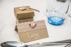 Sand coloured name tags with lace around the top and a baby pink rose in the middle. Also a matching favour box.