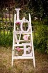 vintage white display piece made with white ladder, pink flowers, clear jars, and huge letters