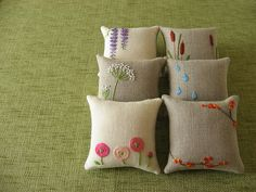 Embroidered pin cushions. I love these. so sweet.