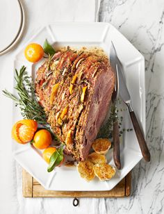 Rows of sliced oranges, garlic, and fresh rosemary infuse this Easter ham recipe with flavor as it bakes. #easterham #hamrecipes #easterdinner #bhg
