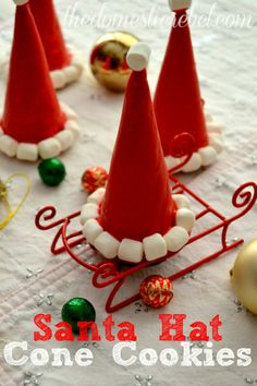 I love these simple Santa Hat Cookie Cones!  Made in minutes and filled with a surprise, guests of any age will love these unique sweets! #santa #christmas #candy #cookies #diy #baking