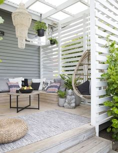 In this Auckland, New Zealand, beach home, a gracious porch has just enough space for an outdoor living room. | Photographer: Larnie Nicolson