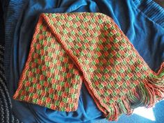 Interlocking block scarf with Red Heart Soft guacamole, toast, & tangerine.  Follow the link for the free pattern.