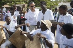 The Obamas in Africa | President Obama speaks with local residents as he tours Goree Island off the coast of Dakar. | Photo: Jim Watson / AFP/ Getty Images
